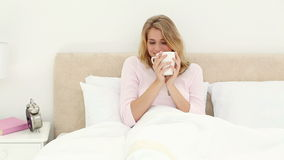 Smiling blonde woman drinking a tea stock video