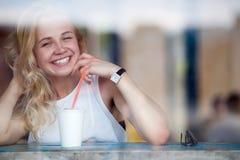 Smiling blonde woman enjoying her milkshake sitting in coffee Stock Images