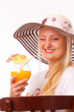 Smiling blonde woman in a hat drinking juice Stock Images
