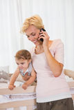 Smiling blonde woman with his son phoning Stock Photo