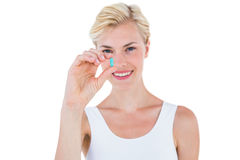 Smiling blonde woman holding blue pill Royalty Free Stock Photo