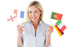 Smiling blonde woman holding european flags Royalty Free Stock Image