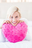 Smiling blonde woman holding heart pillow Royalty Free Stock Images