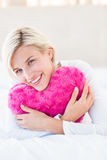 Smiling blonde woman holding heart pillow Stock Photography