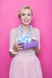 Smiling blonde woman holding purple gift box with ribbon Royalty Free Stock Images