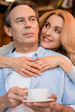 Smiling blonde woman hugging pensive mature man holding tea cup Stock Photo