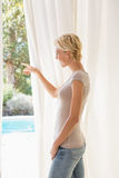 Smiling blonde woman look outside and showing Stock Photography