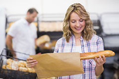 Smiling blonde woman looking at a bread Royalty Free Stock Image