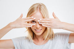 Smiling blonde woman looking at camera through fingers Royalty Free Stock Photo