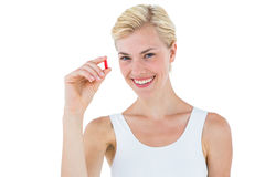 Smiling blonde woman looking at red pill Stock Photo