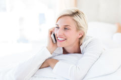Smiling blonde woman lying on the bed and calling on the phone Royalty Free Stock Photography