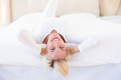 Smiling blonde woman lying on the bed. In her bedroom Stock Photo