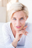 Smiling blonde woman lying on the bed and looking at camera Stock Photography
