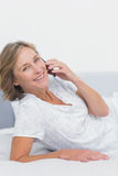 Smiling blonde woman lying on bed making a phone call Royalty Free Stock Photography