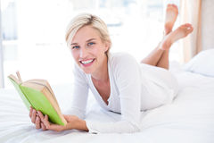 Smiling blonde woman lying on the bed and reading a book Royalty Free Stock Photos