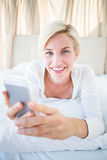 Smiling blonde woman lying on the bed and texting with her mobile phone Stock Photos