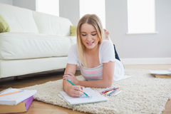 Smiling blonde woman lying on floor sketching on paper Royalty Free Stock Image