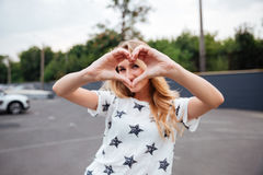 Smiling blonde woman making heart gesture with hands Stock Images