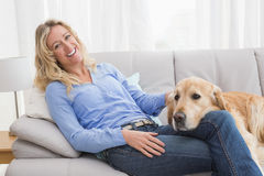 Smiling blonde woman petting her golden retriever Royalty Free Stock Images