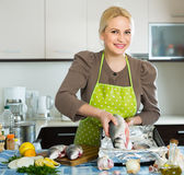 Smiling blonde woman putting pieces of lemon Royalty Free Stock Images