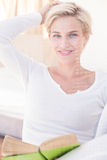 Smiling blonde woman reading a book Stock Photos