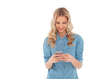 Smiling blonde woman is reading text messages on her smartphone Stock Photography