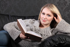 Smiling blonde woman relaxing reading book at home Royalty Free Stock Photography