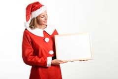 Smiling blonde woman in Santa Claus clothes with white board. Beautiful happy blonde woman in Santa Claus clothes smiling with white board in her hands. Young Royalty Free Stock Images