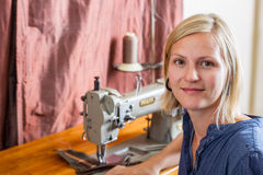 Smiling Blonde Woman At Sewing Machine Stock Photography