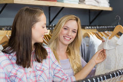 Smiling blonde woman showing clothes to her friend Stock Image