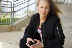 Smiling blonde woman sits outdoor and uses phone Royalty Free Stock Image