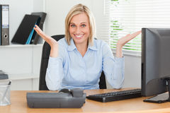 Smiling blonde woman sitting behind desk Stock Photos
