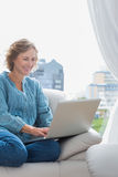Smiling blonde woman sitting on her couch using laptop Royalty Free Stock Photo
