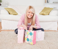 Smiling blonde woman sitting with her shoppin Royalty Free Stock Photo