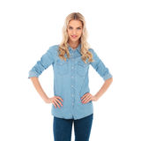 Smiling blonde woman standing with hands on waist Royalty Free Stock Images