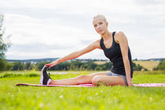 Smiling blonde woman stretching outdoor on the grass Stock Images
