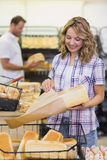 Smiling blonde woman taking a bread in her paper bag Stock Image
