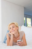Smiling blonde woman using mobile and thinking Stock Photos