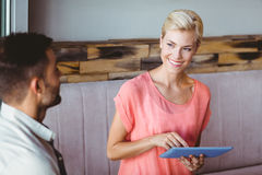 Smiling blonde woman using tablet and looking her boyfriend Stock Photos