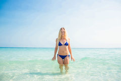 Smiling blonde woman walking into the ocean Royalty Free Stock Photography