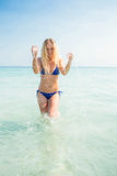 Smiling blonde woman walking into the ocean Stock Photos
