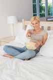 Smiling blonde woman watching TV and eating pop corn Royalty Free Stock Image