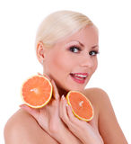 Smiling blonde young woman with orange fruits isolated Royalty Free Stock Image