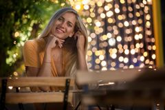 Smiling blonde young woman sitting, with evening fairy lights on the background. Orange dress. Happy beautiful girl royalty free stock photo