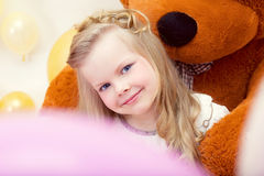 Smiling blue-eyed girl posing with teddy bear Stock Photography