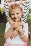 Smiling blue-eyed girl standing near her caring parent stock image