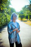 A smiling blue-haired girl in a silvery cloak posing in front of a camera. In the park stock photo