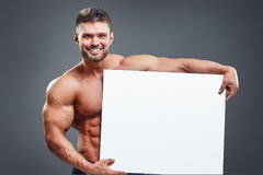 Smiling bodybuilder holding blank white poster Royalty Free Stock Images