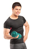 A smiling bodybuilder lifting up a dumbbell Stock Images
