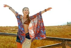 Smiling bohemian girl outdoors in summer evening rejoicing. Bohemian vibe vacation. smiling trendy bohemian girl in jeans shorts and cape outdoors in the summer royalty free stock photo